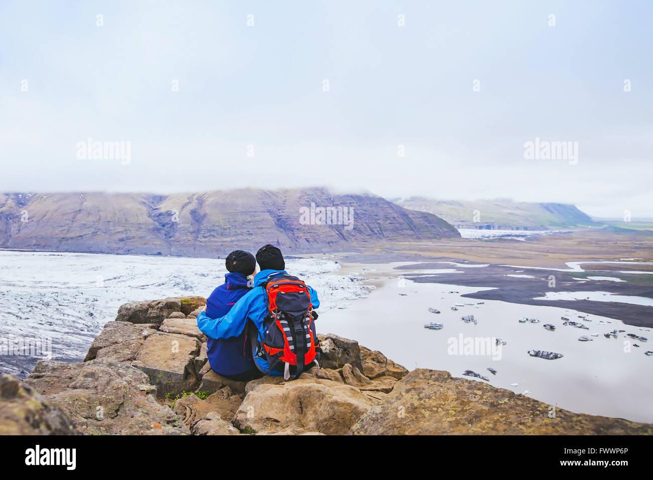 Couple de randonneurs voyager en Islande, deux backpackers enjoying view de paysage de montagne et glacier Photo Stock