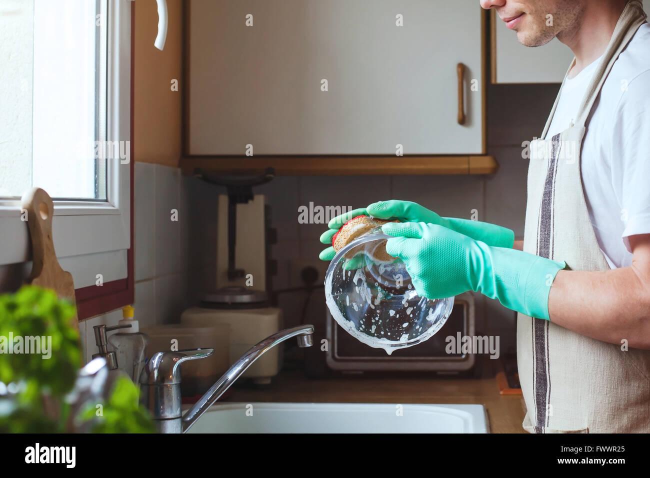 L'homme lave la vaisselle dans l'évier de cuisine à la maison, près des mains avec du savon Photo Stock