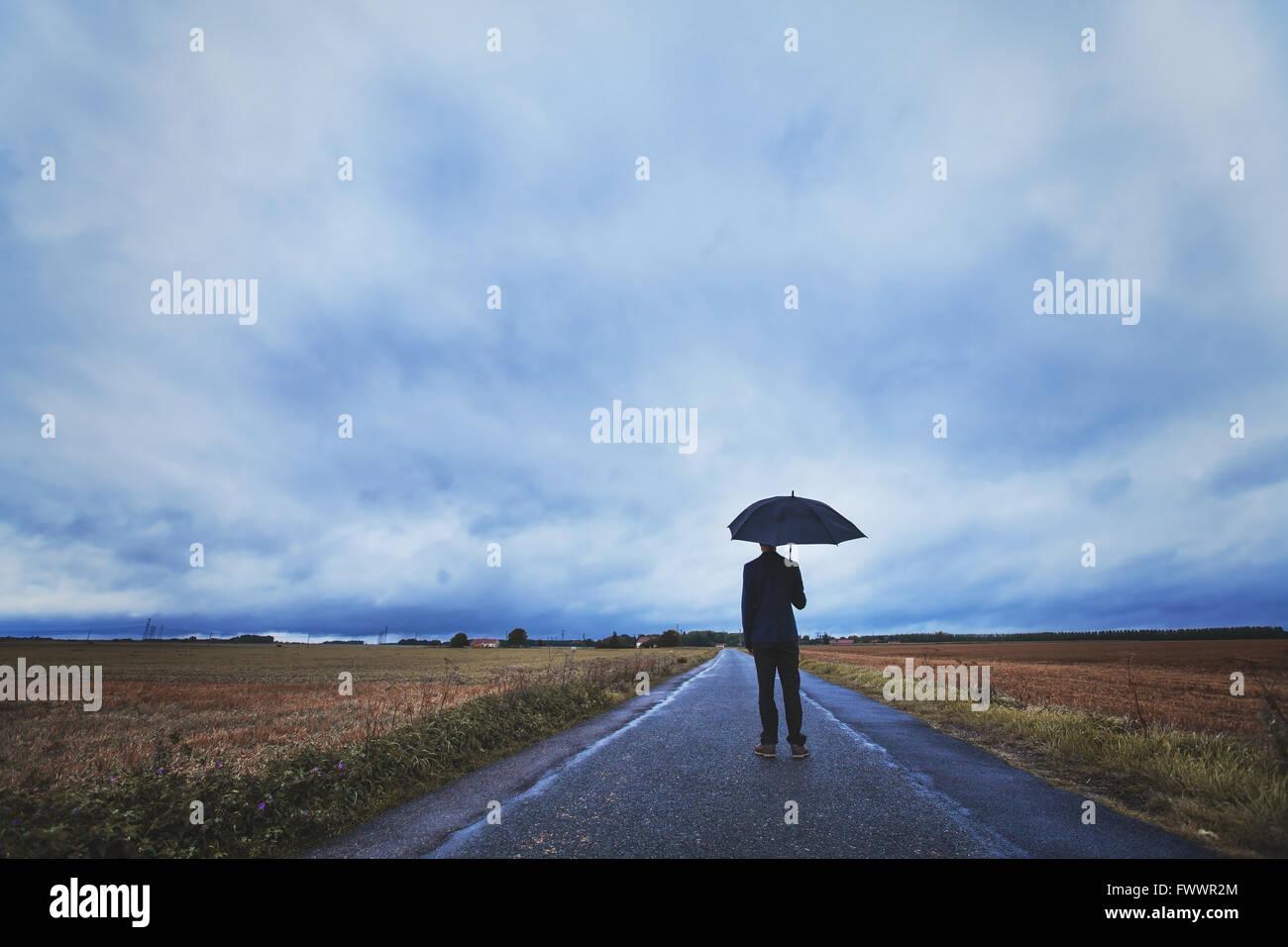 Concept de la psychologie, l'homme debout avec parasol sur la route, les peurs et la solitude Banque D'Images