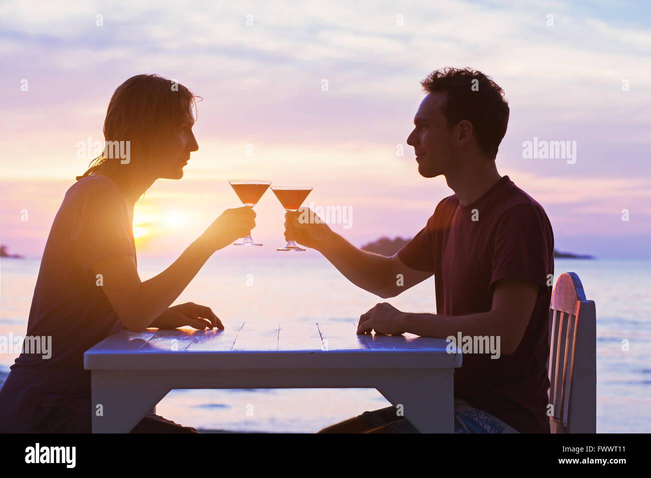 Couple in restaurant, boire des cocktails sur la plage au coucher du soleil Photo Stock