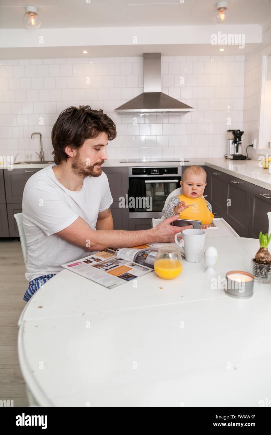 La Suède, père et fils (12-17 mois) assis dans la cuisine Photo Stock