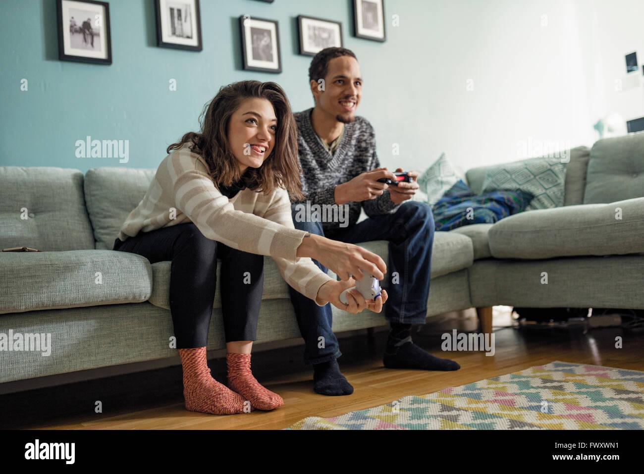 La Suède, jeune couple jouant des jeux vidéo dans la salle de séjour Photo Stock