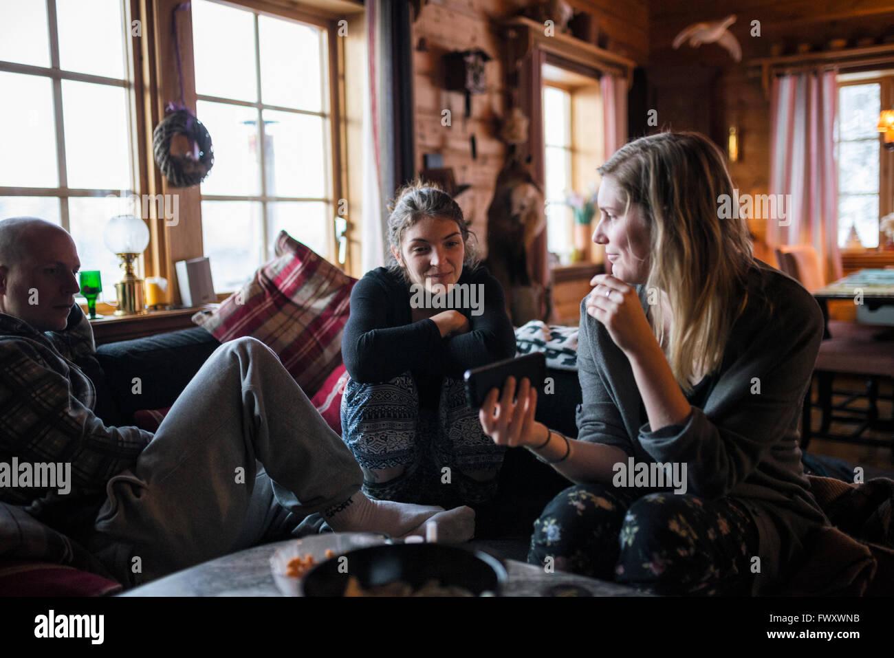 La Suède, jeune femme montrant smart phone à des amis en log cabin Photo Stock