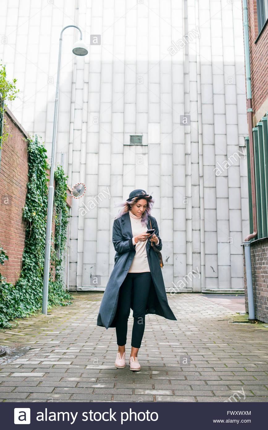 La Suède, Vastra Sweden, young woman wearing long pardessus et chapeau melon à l'aide de smart phone Photo Stock