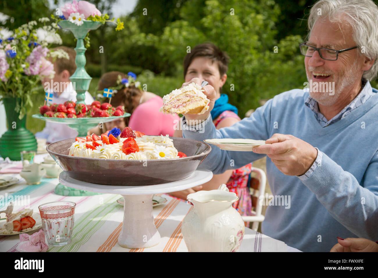 La Suède, Skane, famille avec un enfant (8-9) ayant plein air dessert Photo Stock