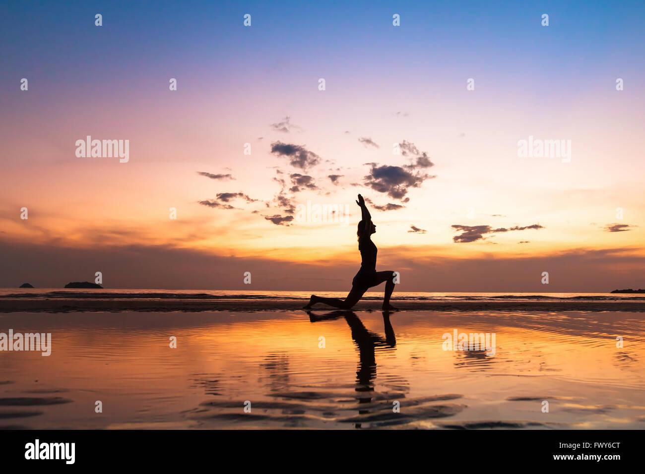Belle exercice de yoga sur la plage au coucher du soleil, avec fond copyspace Photo Stock