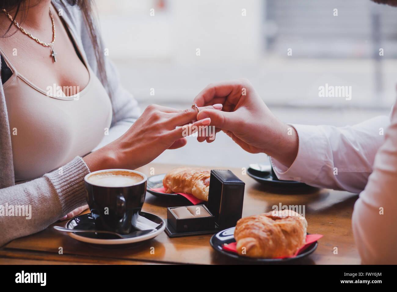 Bague de fiançailles, à la proposition de café, près des mains de l'homme et de la femme Photo Stock