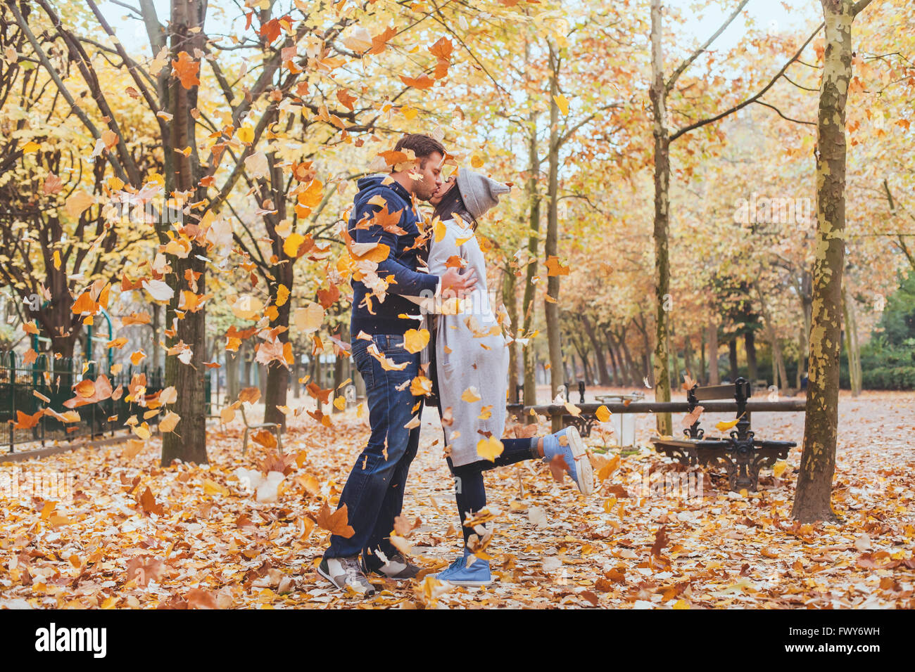 Automne baiser, jeune couple d'amoureux dans le parc avec les feuilles qui tombent Photo Stock