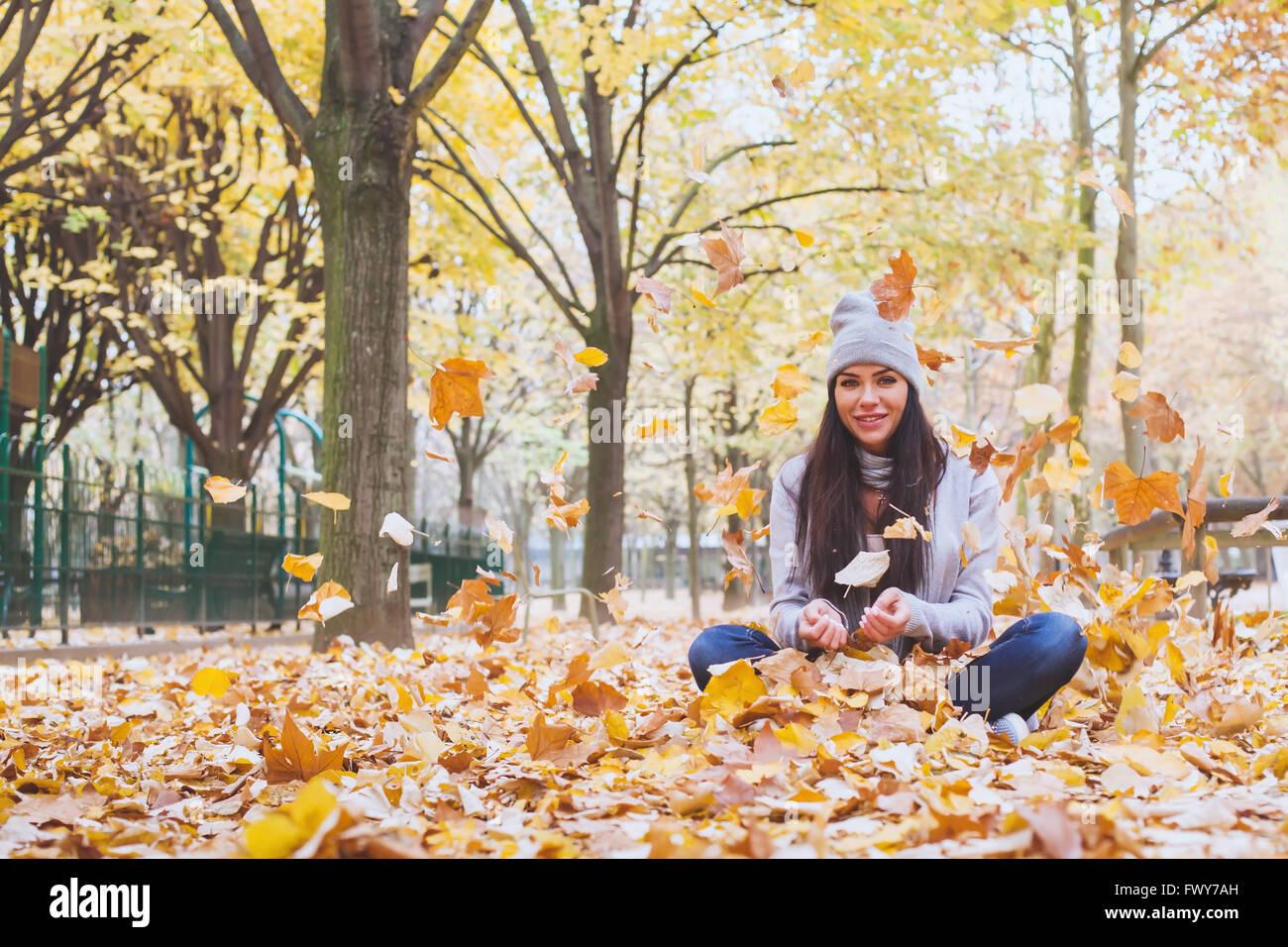 Autumn park, belle femme souriante et la chute des feuilles jaunes Photo Stock