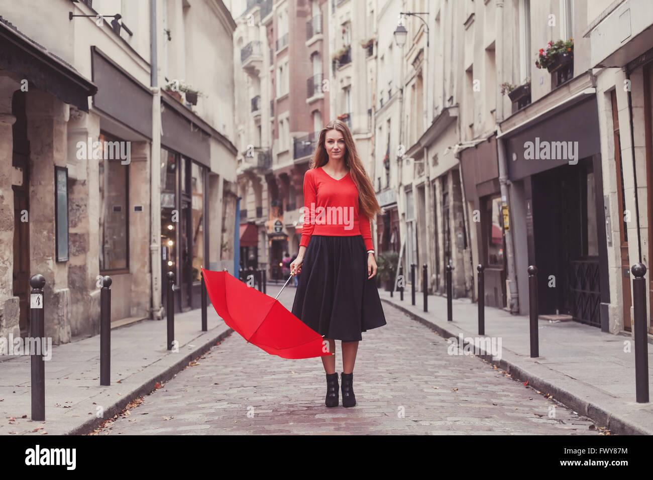 Belle femme, portrait de fille avec parapluie rouge debout sur la rue de Paris Photo Stock