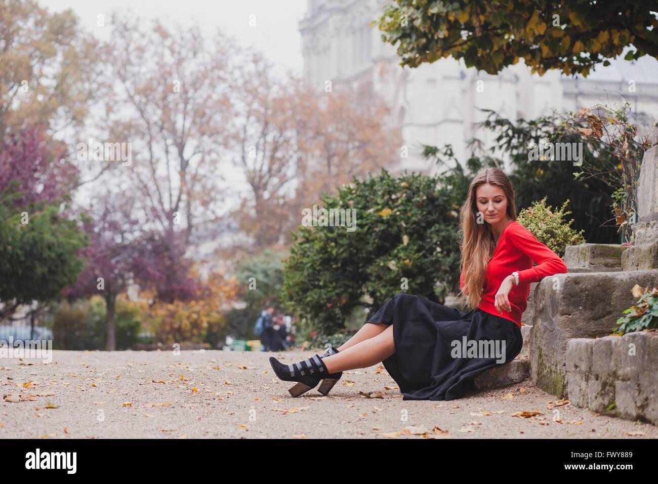 Belle femme en rouge, portrait of caucasian fashion jeune modèle aux cheveux longs assis tout seul, la psychologie Photo Stock