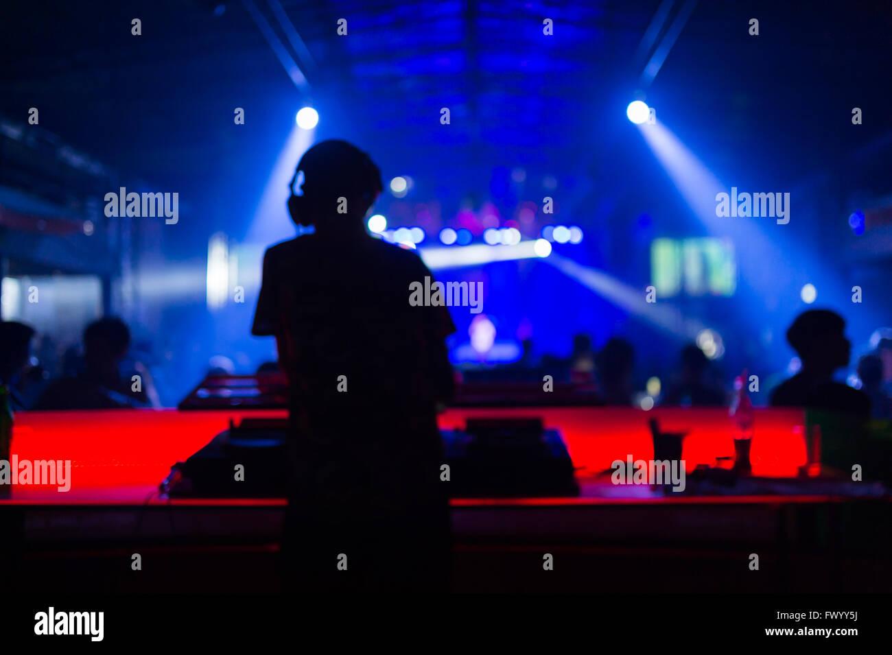 Arrière-plan flou: Club, discothèque DJ jouer et mixer de la musique pour foule de gens heureux. Photo Stock