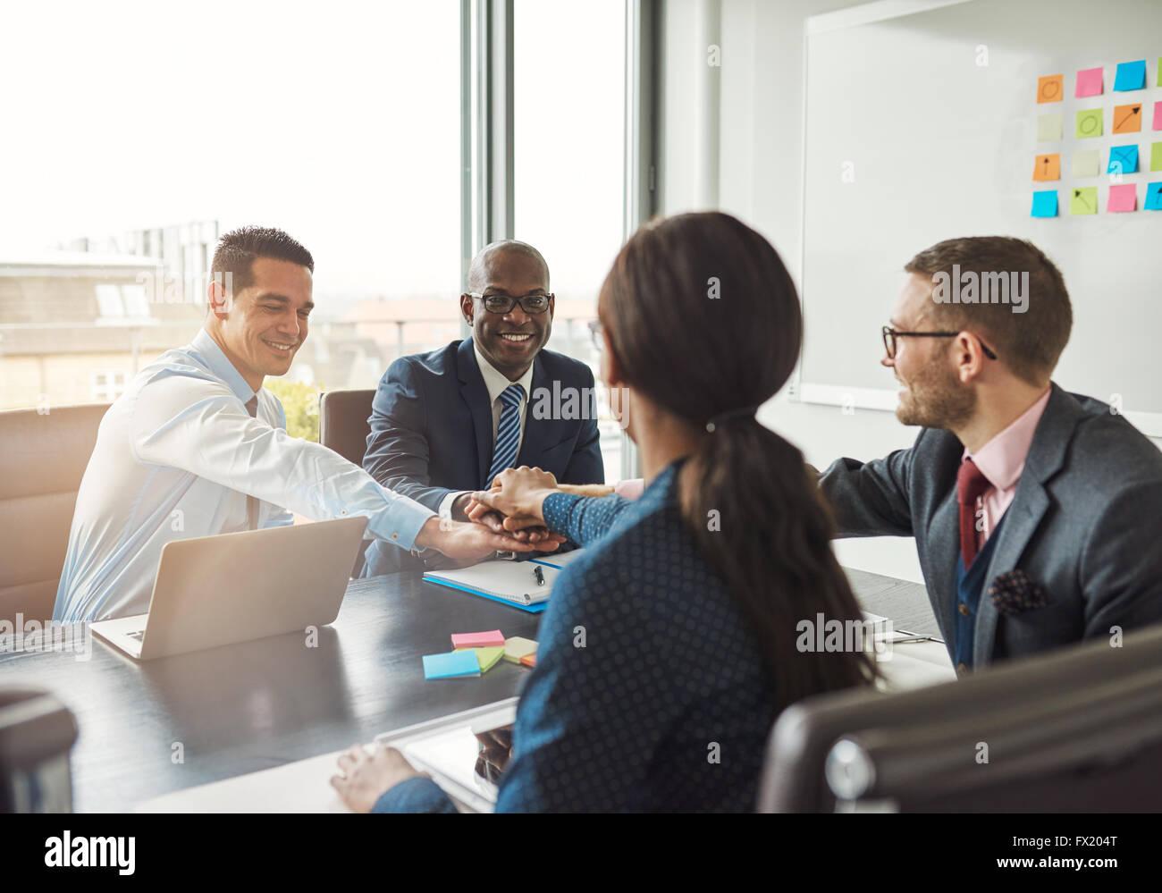 L'équipe entreprise multiraciale réussie travailler ensemble affirment leur engagement en liant les Photo Stock