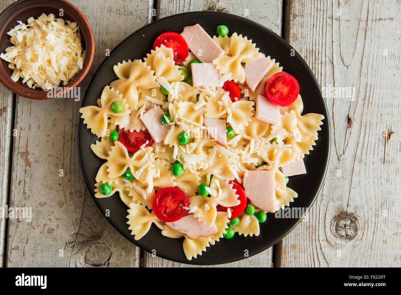 Des pâtes avec du jambon et fromage Tomates pois vert Photo Stock