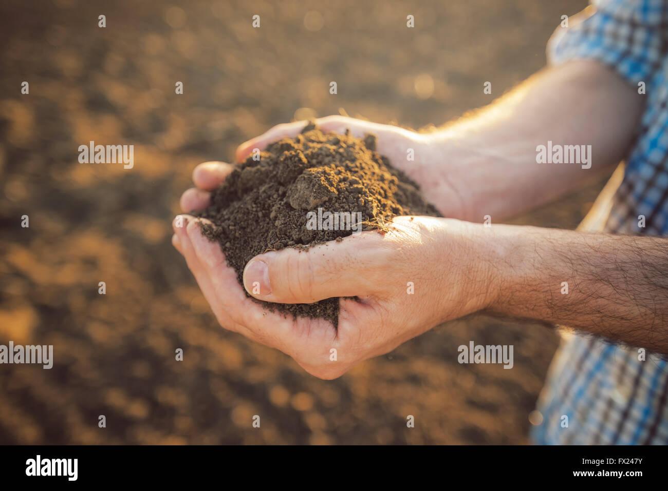 Farmer holding pile de sols arables en mains, responsable et durable de la production agricole, Close up avec selective Photo Stock