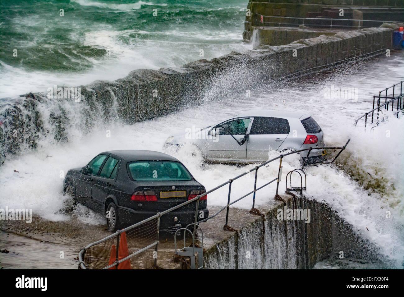 Mousehole, Cornwall, UK. 10 avril 2016. Météo britannique. Le moment la force de la mer presque pousse cette voiture dans le port de Mousehole, au cours de cette matinée d'énormes vagues. Crédit: Simon Maycock/Alamy Live News Banque D'Images