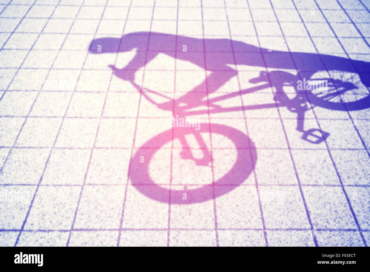 Ombre floue aux couleurs rétro d'un adolescent équitation un vélo BMX. Photo Stock