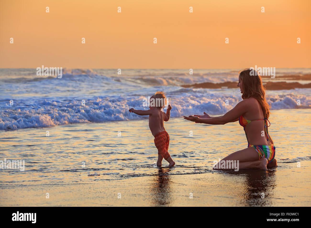 Piscine familiale in sea beach surf Happy mother, baby son Première étape - tout-petit run pour océan Photo Stock