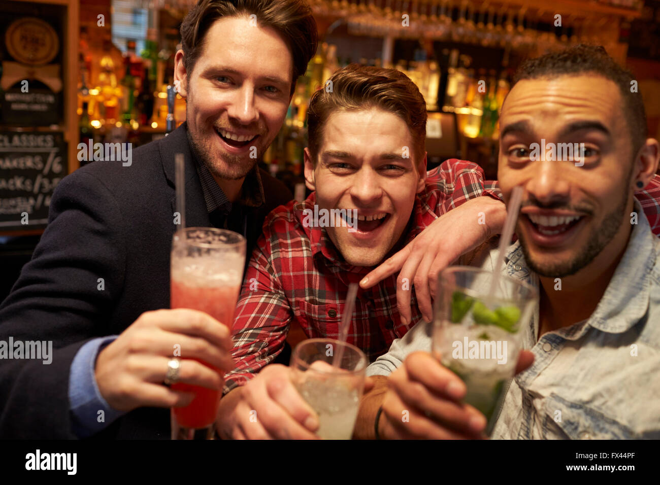 Réunion d'amis masculins pour prendre un verre en soirée au bar à cocktails Banque D'Images