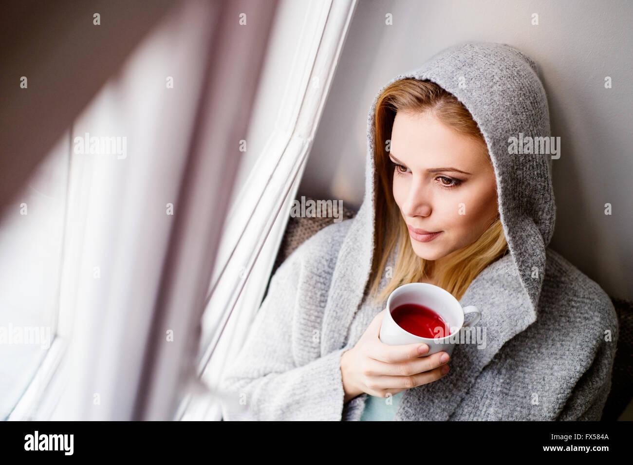 Femme sur appui de fenêtre tenant une tasse de thé Photo Stock