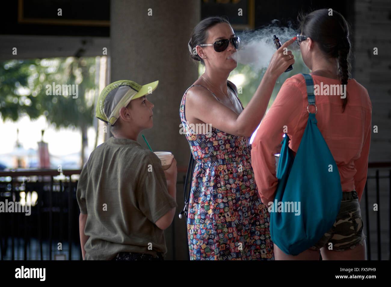Le tabagisme passif. Mère fumeurs de cigarettes et de fumée e de soufflage en visage d'enfant. Photo Stock