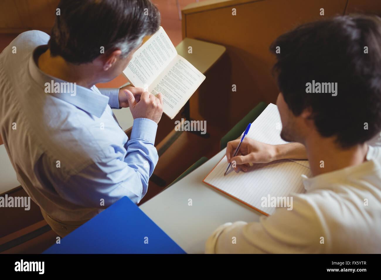 Le professeur aider un étudiant avec son étude Photo Stock