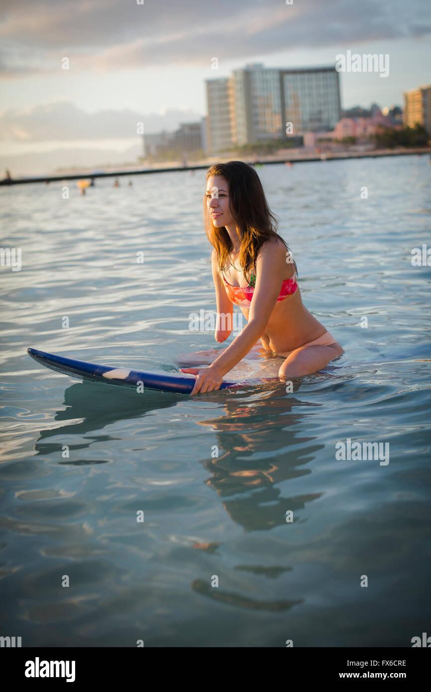 Mixed Race amputee assis sur une planche de surf dans la région de ocean Banque D'Images