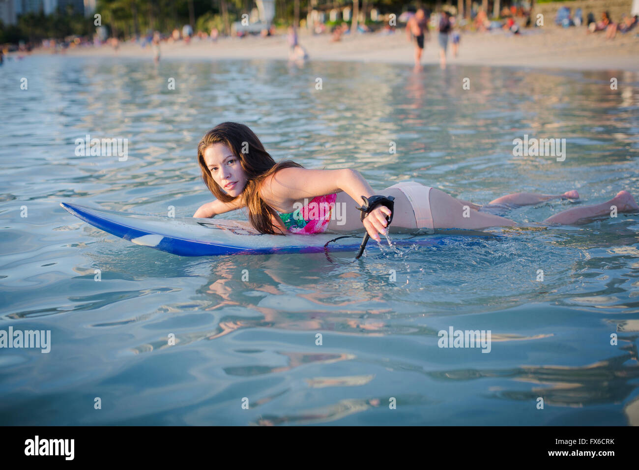 Mixed Race amputee natation with surfboard Banque D'Images