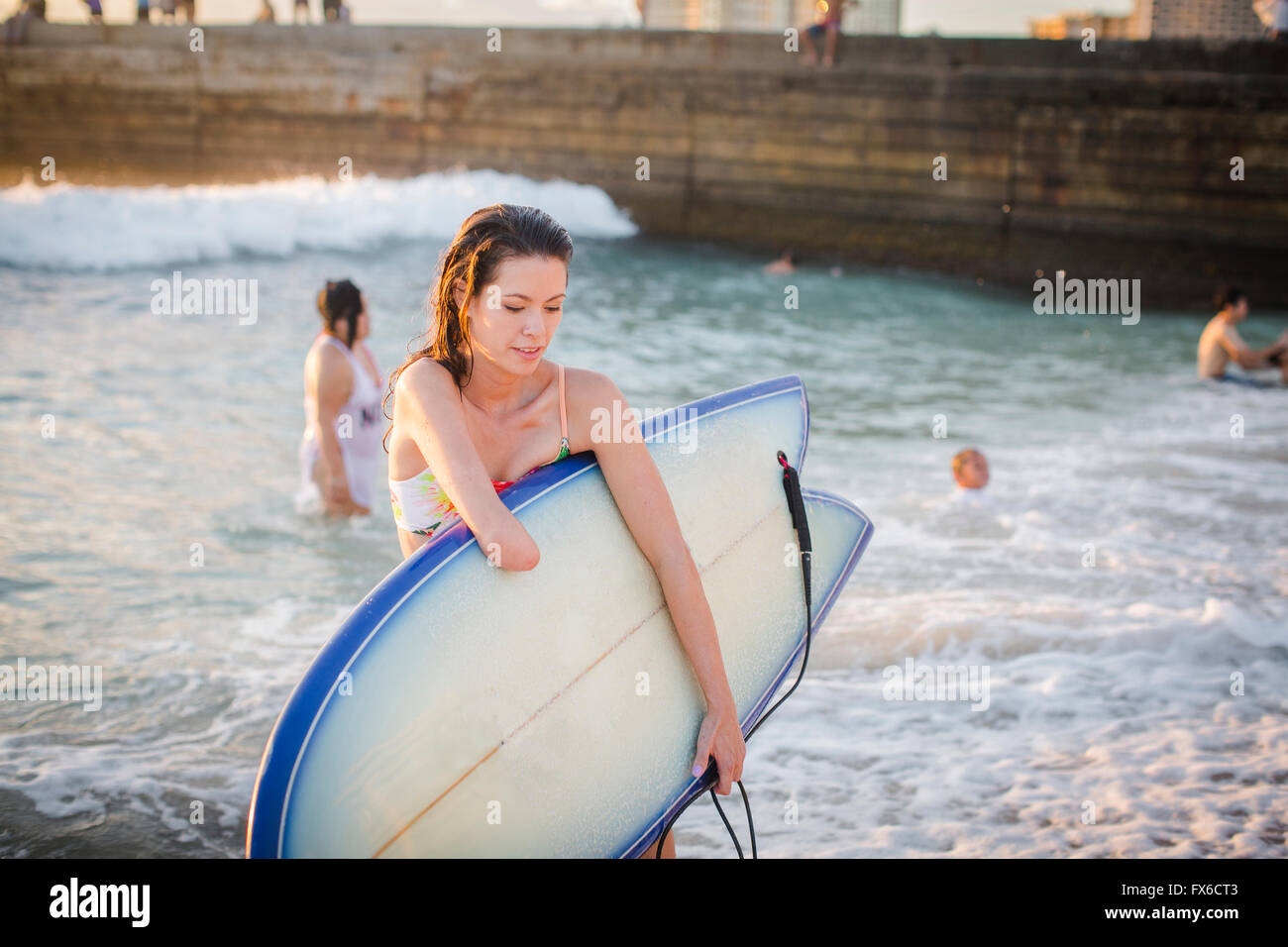 Mixed Race amputee transportant surfboard on beach Banque D'Images