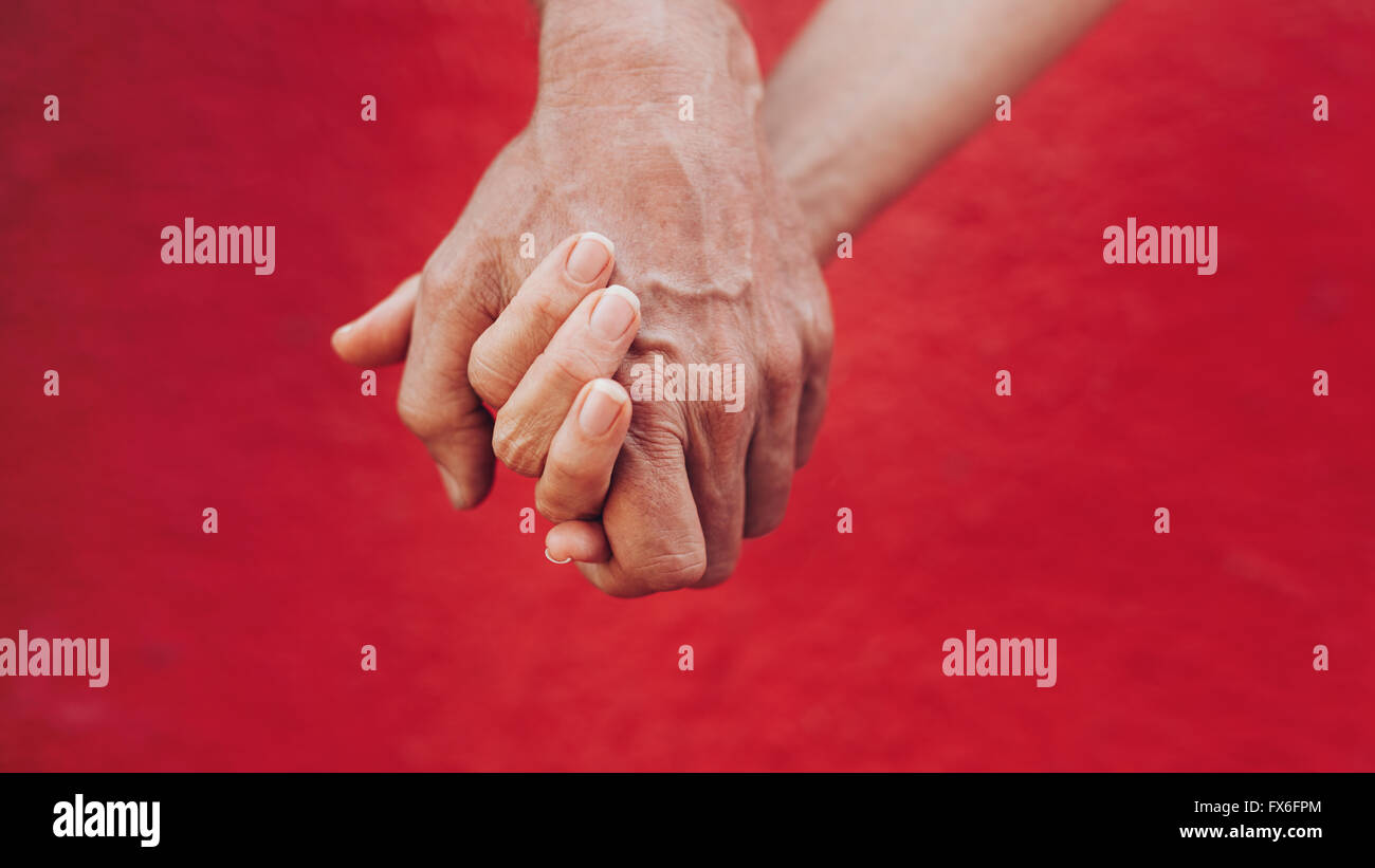 Close up of man and woman holding hands contre fond rouge. Affectionate couple holding hands. Photo Stock