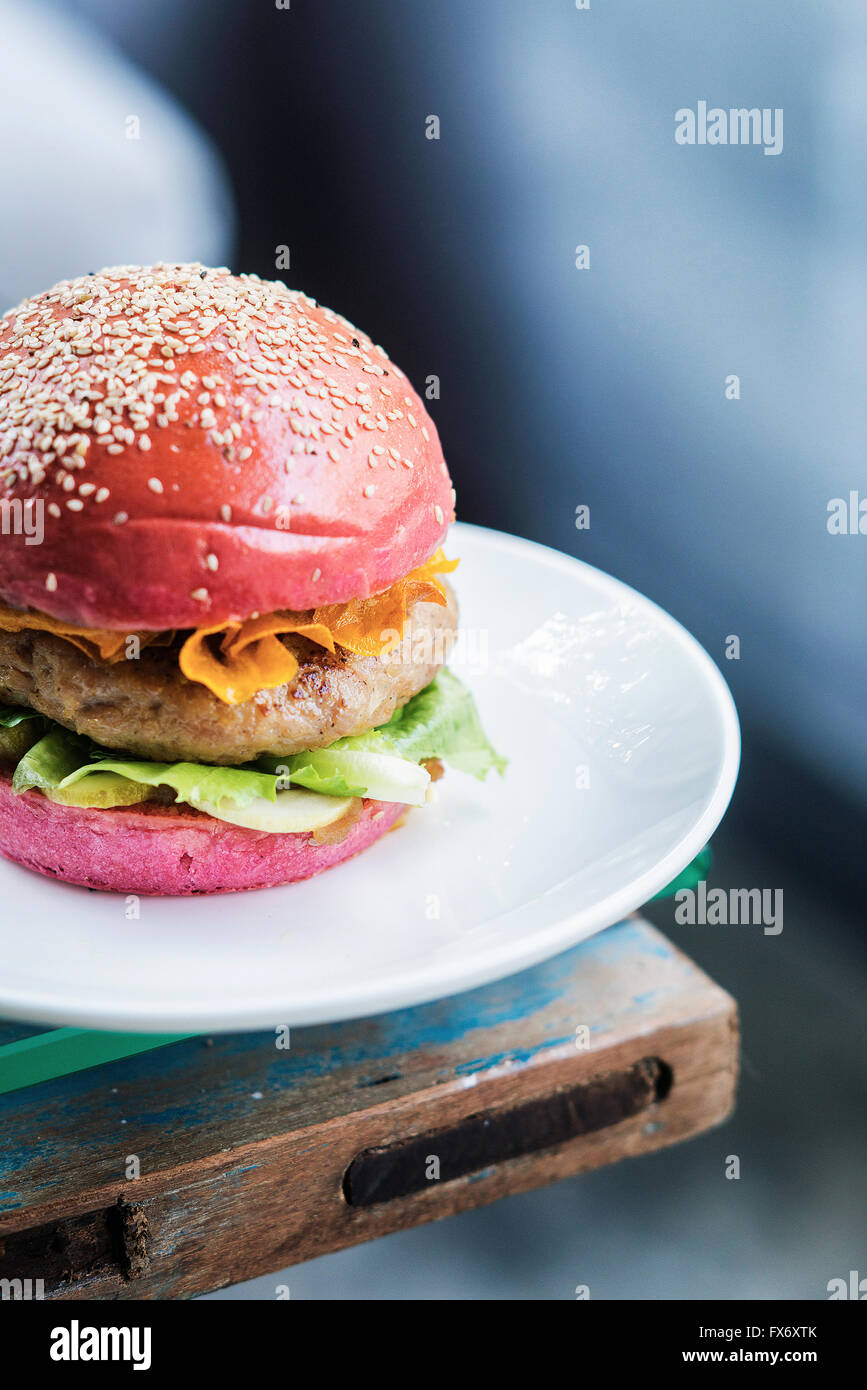 Burger de poulet avec les cornichons et les chips de betterave en pain bun Photo Stock