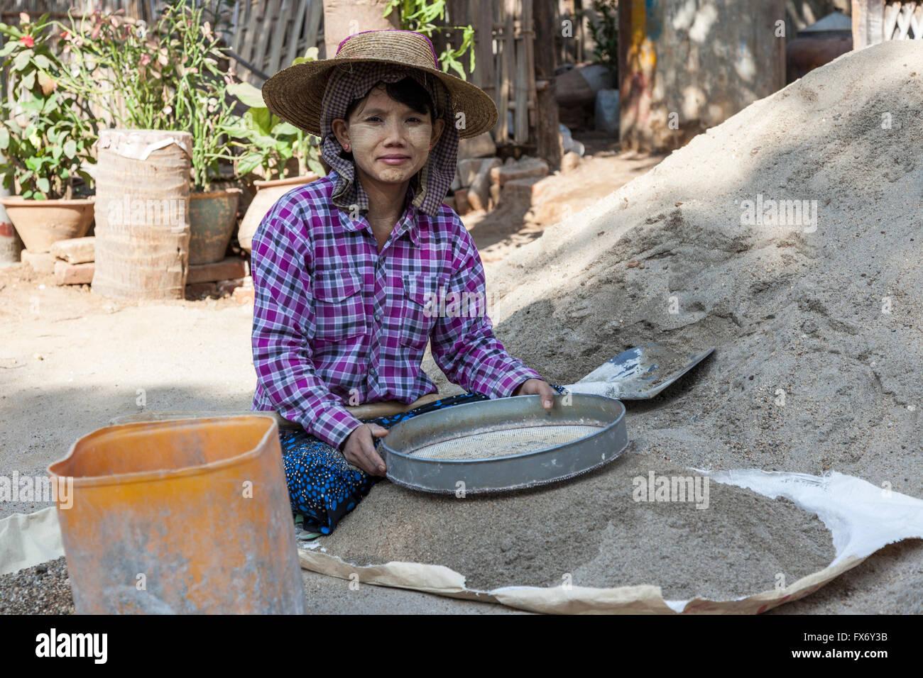 À New Bagan, un apprenti jeune femme préparer le mortier pour des ouvriers sur un chantier de construction Photo Stock