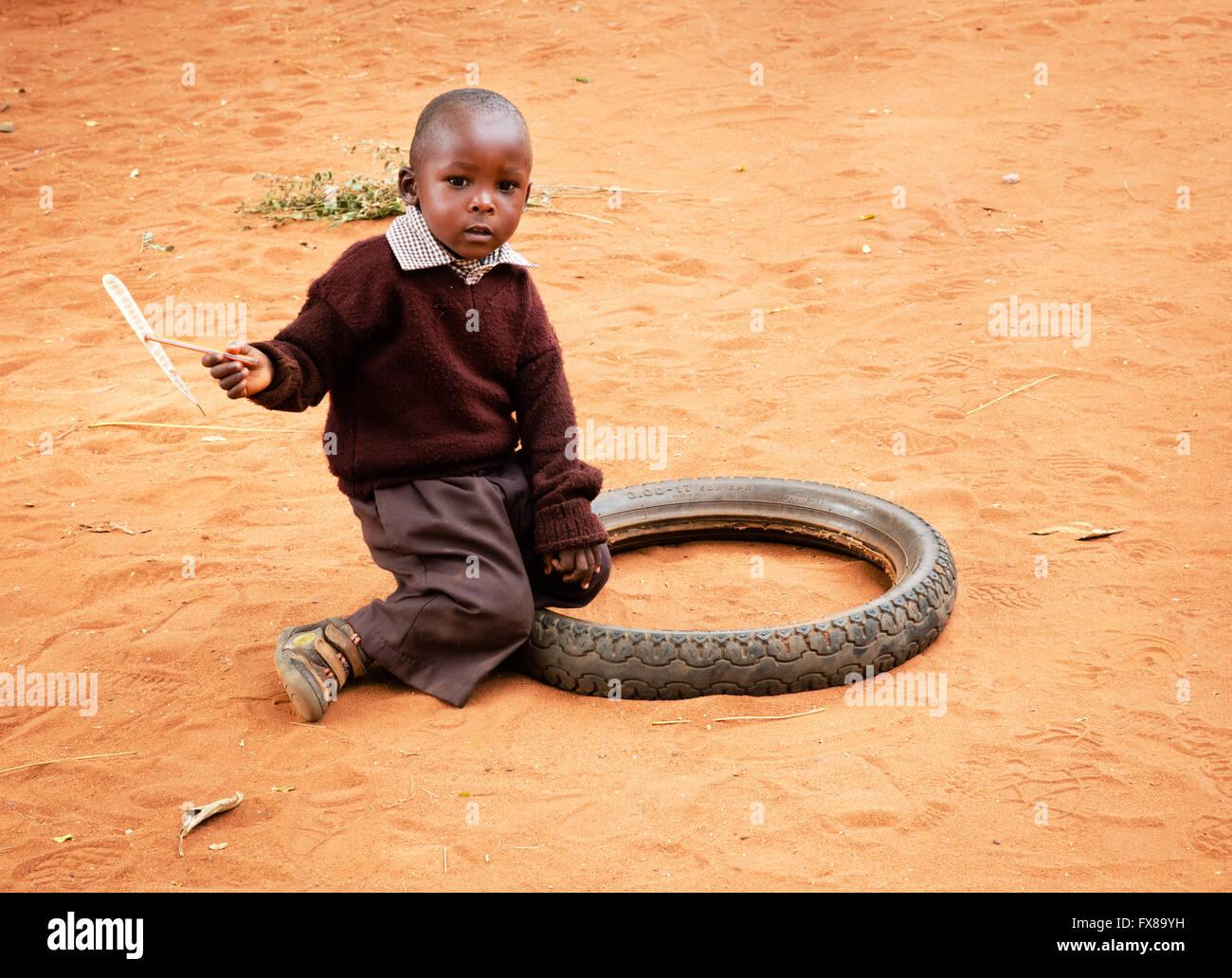 Un jeune écolier jouant avec des jouets de fortune d'un bâton et de l'hélice un vieux pneu Photo Stock