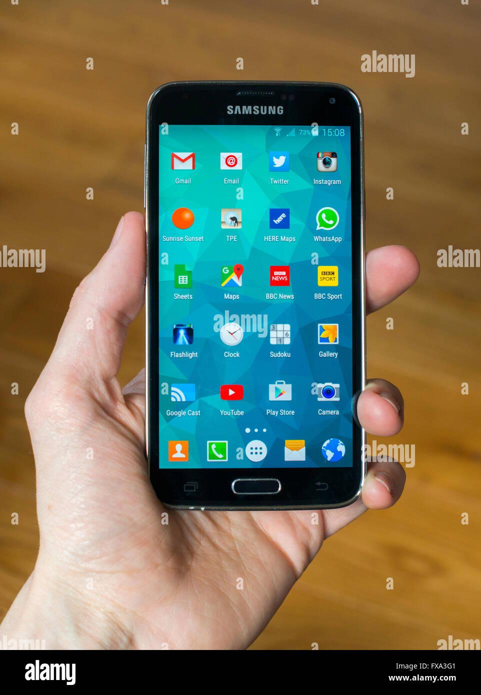 Une main tenant un Samsung S5 Téléphone avec l'écran d'accueil ouverte montrant des applications. Photo Stock