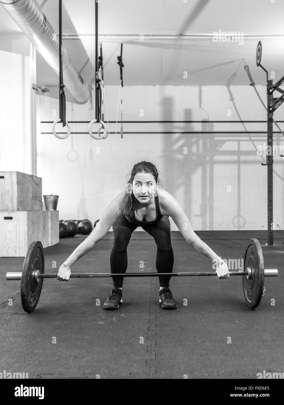 Photo d'une jeune femme à un sport crossfit soulevant un barbell. Photo Stock