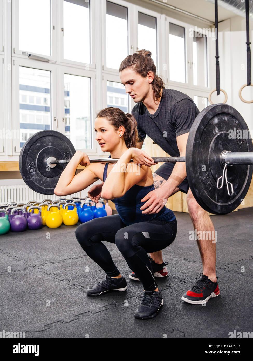 Photo d'une jeune femme à un sport crossfit faisant s'accroupit tandis que ses montres de l'instructeur Photo Stock