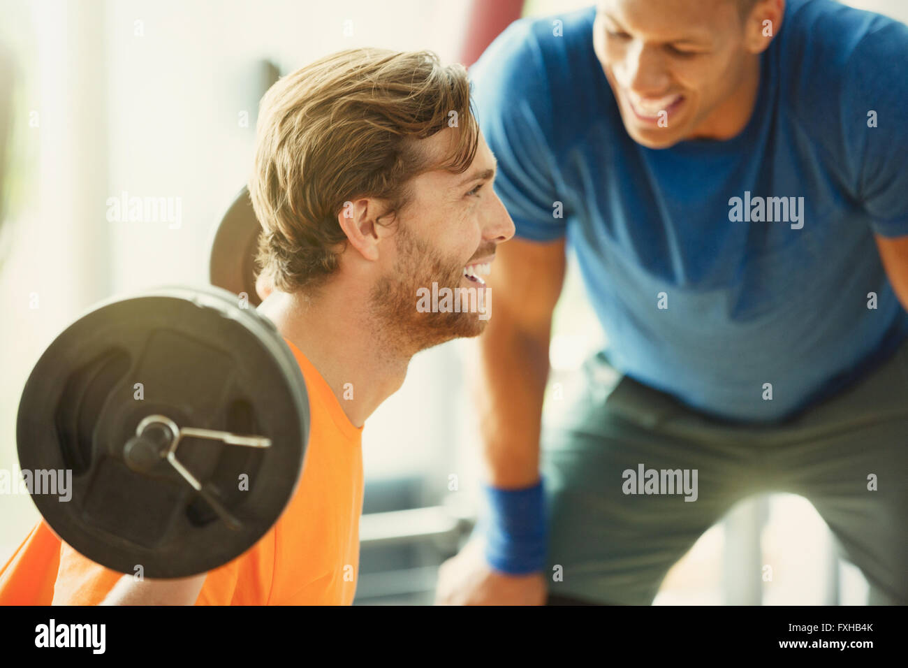 Entraîneur personnel encourageant man doing barbell squats at gym Photo Stock