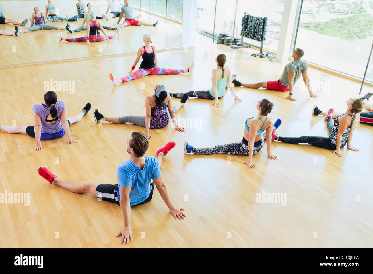 High angle view classe d'exercice qui s'étend avec les jambes à gym Photo Stock