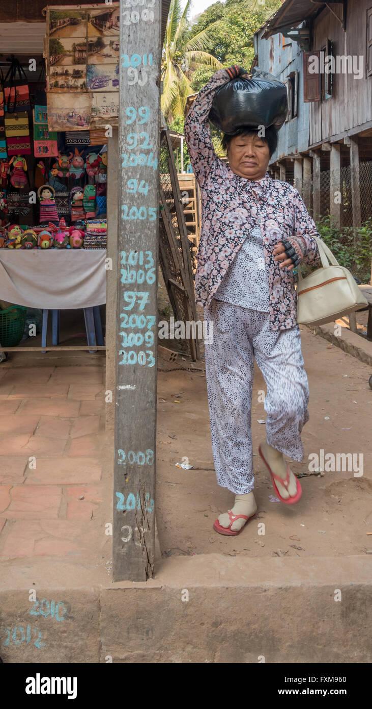 Marqueur sur une maison sur pilotis montrant les niveaux d'eau des crues à Chau Doc, au fil des années avec une personne portant un sac sur sa tête, Delta du Mekong, Vietnam Banque D'Images