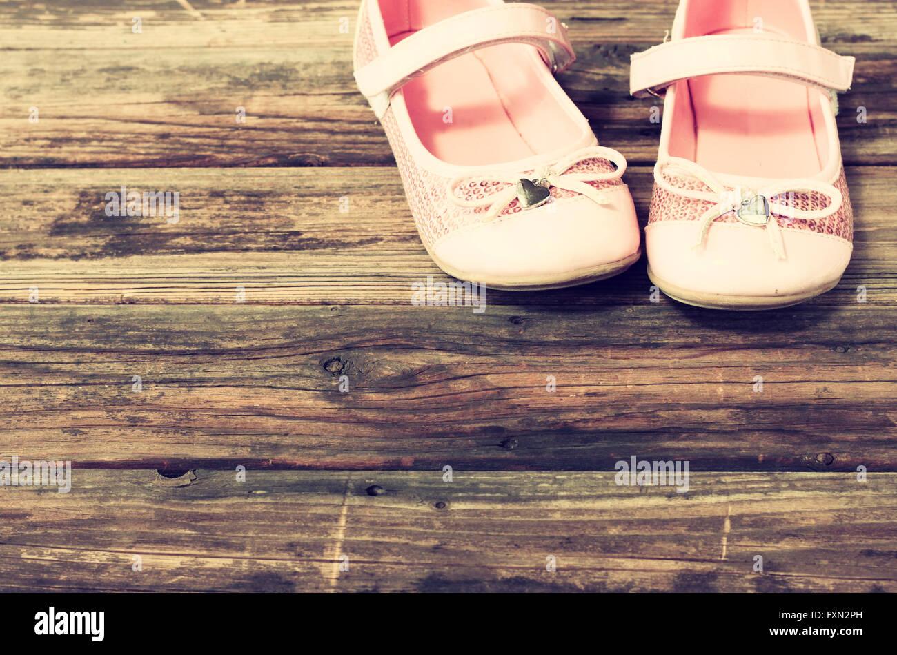 Chaussures fille sur terrasse en bois-de-chaussée. image filtrée. Photo Stock