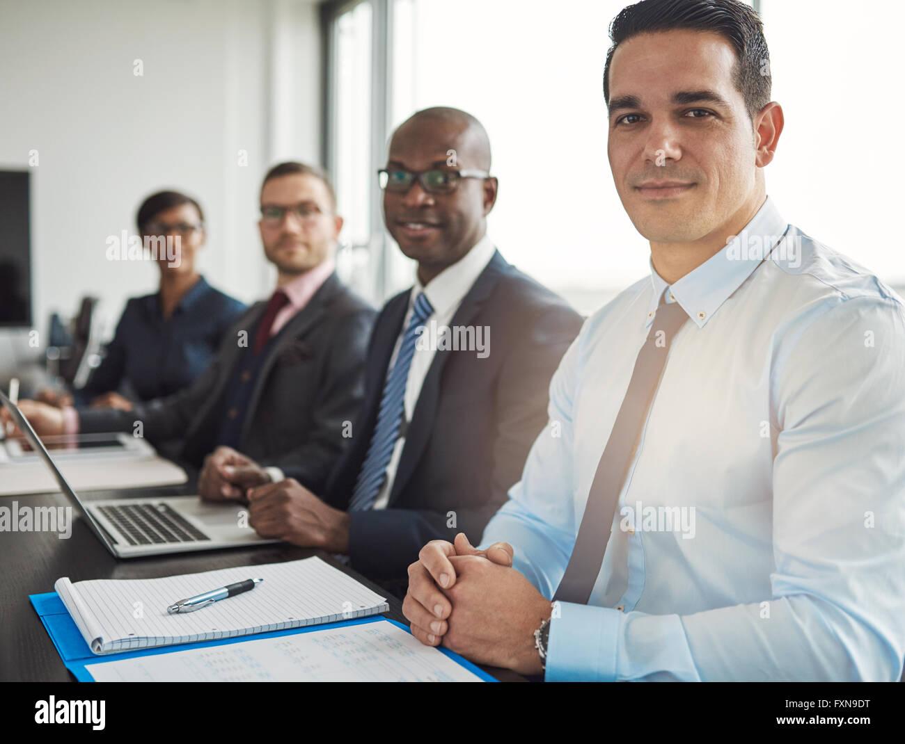 Calme groupe diversifié de quatre hommes d'affaires assis à table avec ordinateur et portables en face de grande fenêtre de bureau avec lig Banque D'Images