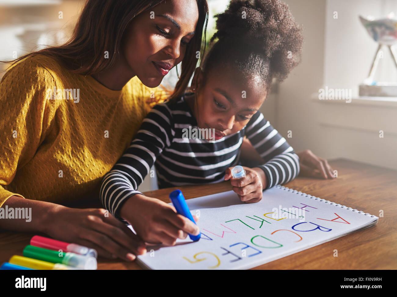 Petite fille écrit l'alphabet avec la mère à la maison Photo Stock