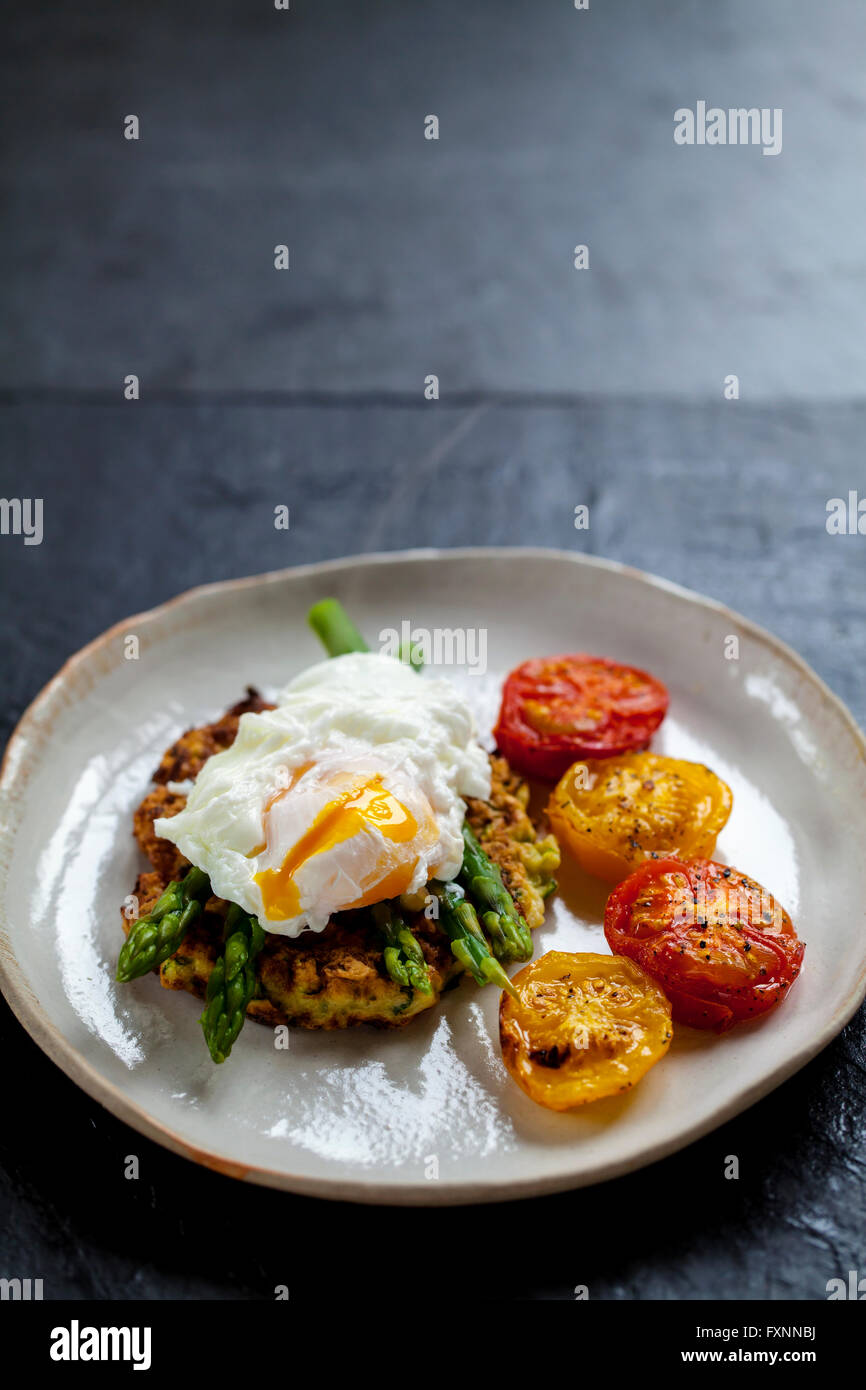 Rosti de courgettes, oeuf poché, asperges et tomates rôties Photo Stock