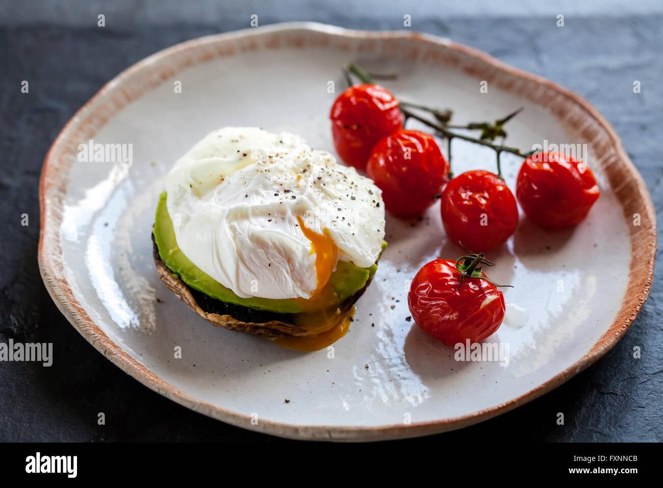 Le petit-déjeuner, les champignons avec de l'avocat et œufs pochés et faites rôtir les tomates Photo Stock
