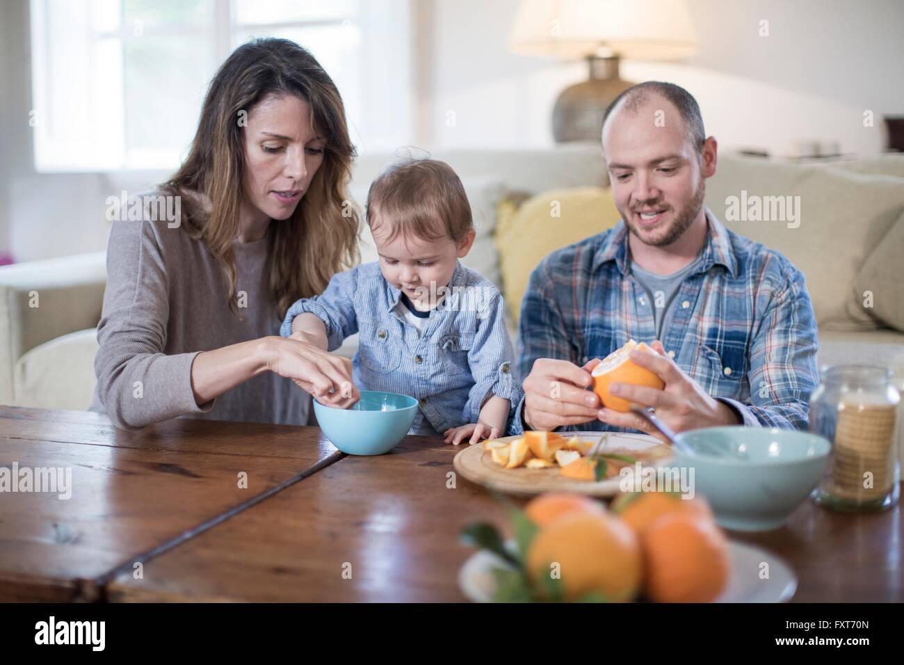 Les parents en train de déjeuner avec baby boy, peeling orange Photo Stock