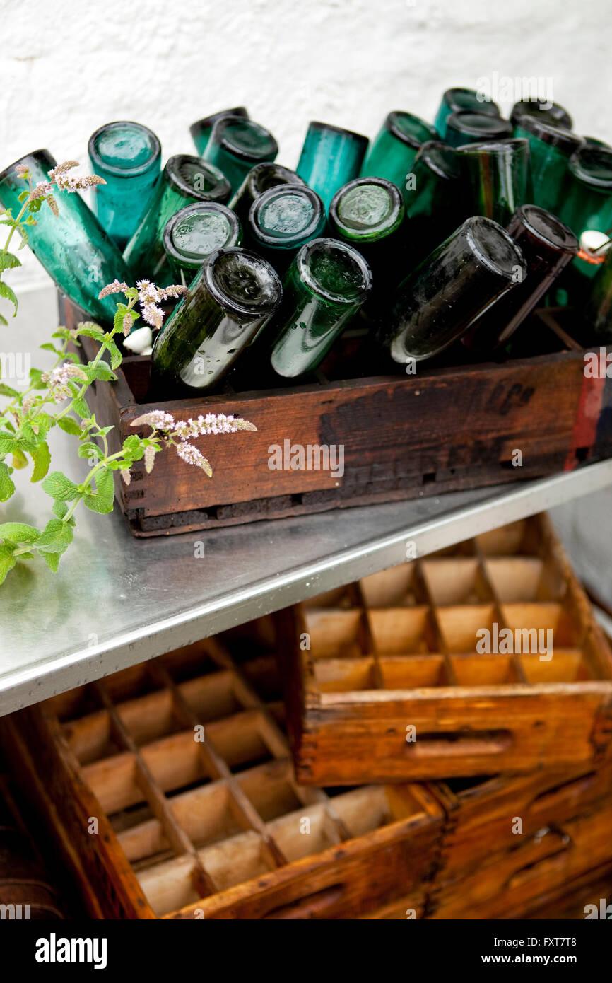 Des caisses en bois avec tête en bas vintage bouteilles sur terrasse dans la pluie Photo Stock