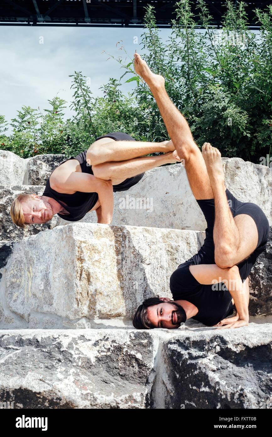Deux hommes pratiquant de yoga avancée headphones étape parc Photo Stock