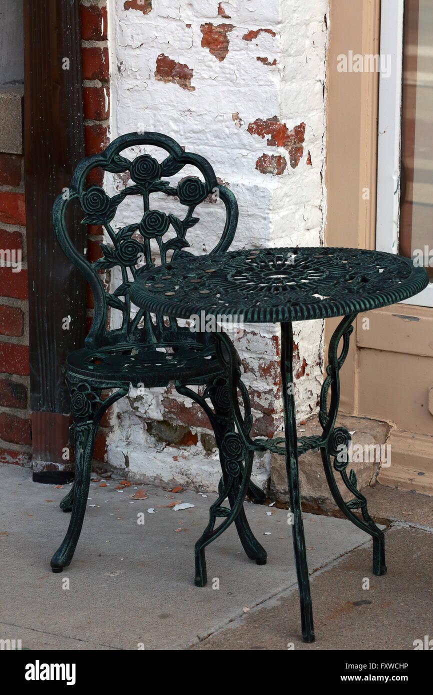 table et chaise en fer forgé avec rose motif devant un mur avec de
