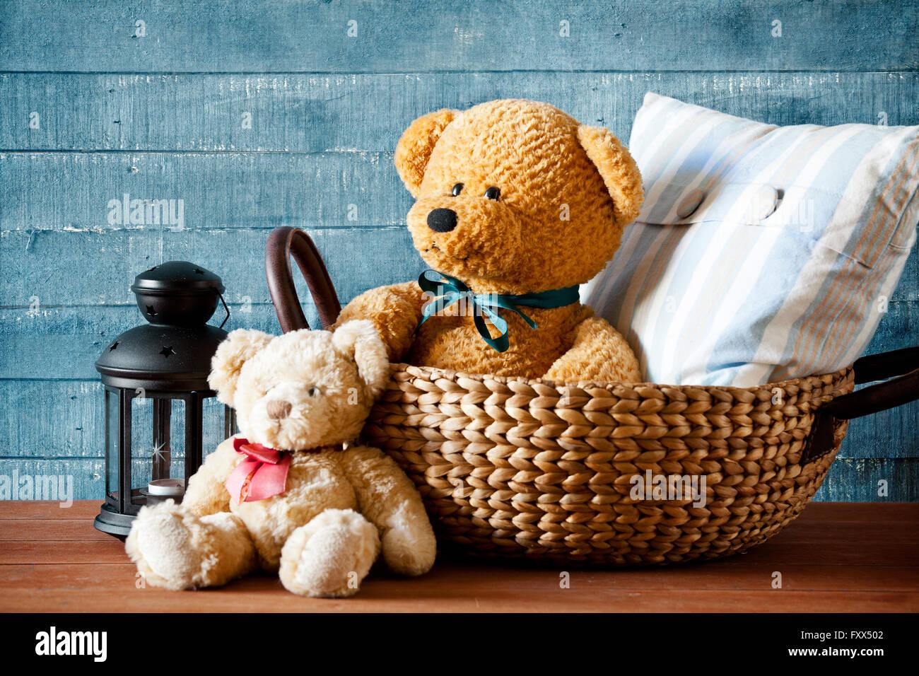 Mignon ours en peluche dans un panier sur une table en bois Photo Stock