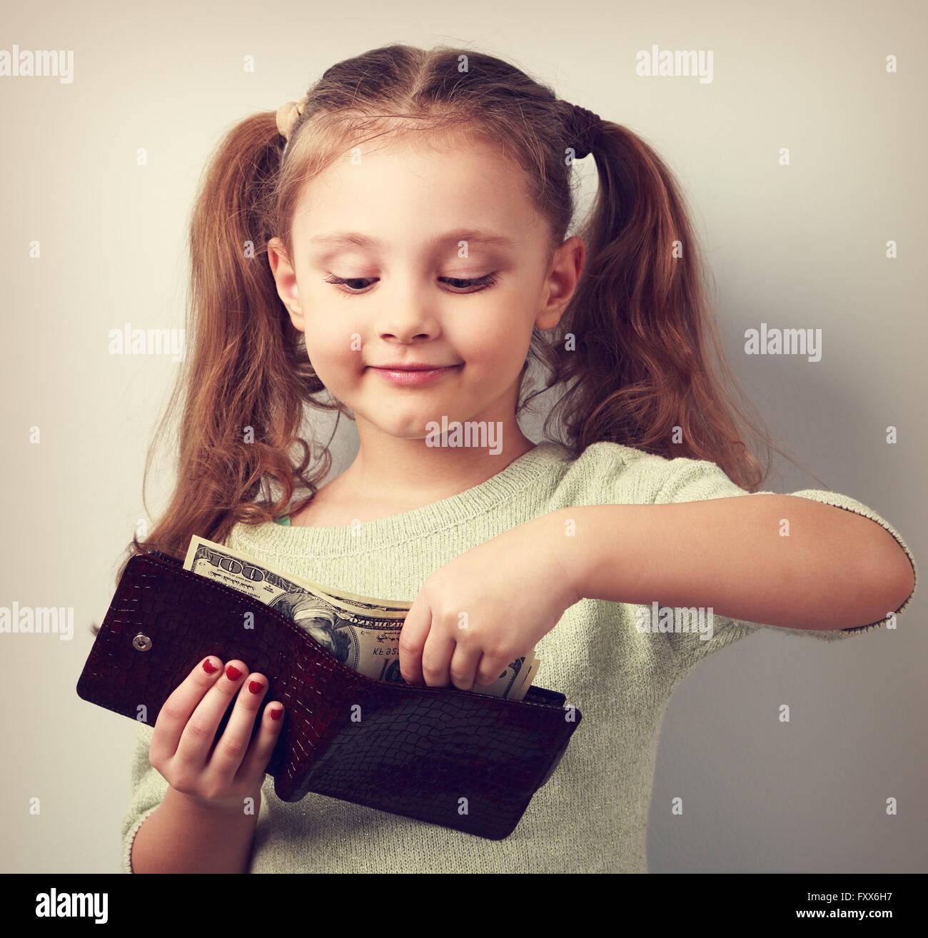 Petit enfant cute girl taking dollars de la mère porte-monnaie et à heureux. Tonique closeup portrait Photo Stock